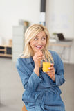 Playful woman enjoying a glass of orange juice Stock Photos