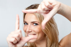Playful woman framing her face with her fingers Stock Photo