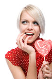 Playful woman with a heart-shaped lollipop Stock Photography