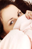 Playful woman hiding her face under the sheet. Royalty Free Stock Photo