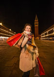 Playful woman holding shopping bags on Piazza San Marco, Venice Stock Images