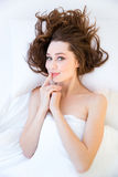 Playful woman lying in bed and touching her lips Royalty Free Stock Image