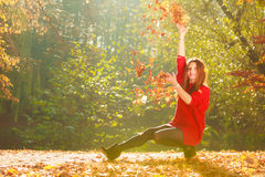Playful woman outdoors playing with leaves. Stock Photos
