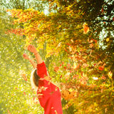 Playful woman outdoors playing with leaves. Royalty Free Stock Photo
