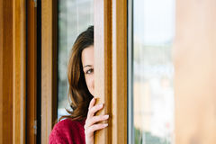 Playful woman peeking through home window Royalty Free Stock Photo