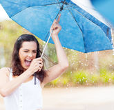 Playful woman in rain. Playful young woman holding umbrella in the rain Stock Photography