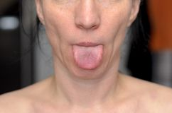 Playful woman sticking out her tongue stock image