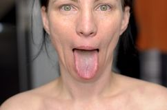 Playful woman sticking out her tongue stock photos