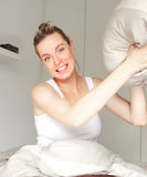 Playful woman throwing a pillow. Beautiful playful woman sitting in her bed poised to throw a pillow during a mock fight with a look of glee on her face Stock Photography
