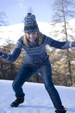 Playful woman throwing snow in forest Royalty Free Stock Photography
