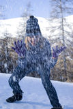 Playful woman throwing snow in forest Stock Photos