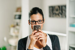 Playful woman using smartphone at home Royalty Free Stock Image