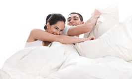 Playful young beautiful couple with pillows Royalty Free Stock Images