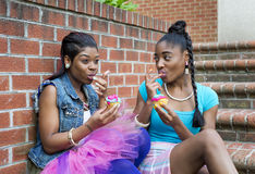 Playful Young Black Women Sitting together. Beautiful sexy young Black Women Posing together on Brick stairs and walkway while eating colorful cupcakes Royalty Free Stock Photography
