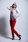 Playful young blonde in glasses and red jeans Stock Image