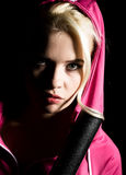 Playful young blonde in a tracksuit holding baseball bat Stock Photos
