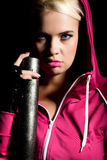 Playful young blonde in a tracksuit holding baseball bat Royalty Free Stock Images