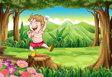 A playful young boy at the forest standing above the stump Royalty Free Stock Photos