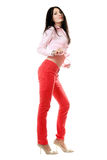 Playful young brunette in red jeans Stock Image