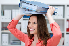 Playful young business clerk with folders. Playful young female business clerk with folders balanced on her head smiling happily Stock Photography