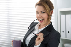 Playful young businesswoman giving a wink Royalty Free Stock Image