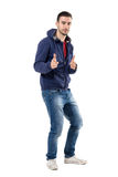 Playful young casual man in sweatshirt with finger gun gesture aiming at camera. Full body length portrait isolated over white studio background stock photos