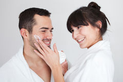 Playful young couple applying cream Stock Photos