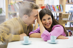 Playful young couple with coffee cups on desk in library Stock Photos