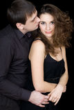 Playful young couple flirting. And hugging. Isolated on black Royalty Free Stock Photography