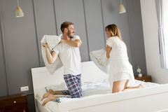 Playful young couple having pillow fight on bed Stock Image