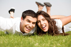 Playful young couple laying down. In a green grass field,park outdoor Royalty Free Stock Photos