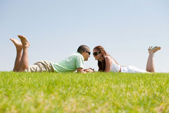 Playful young couple laying on a grass lawn. And looking each otehr Royalty Free Stock Photos