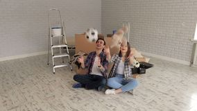Playful young couple moving to a new apartment. Happy young couple sitting on the floor in a new apartment among cardboard boxes and throw up a soccer ball and stock video