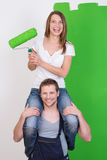 Playful young couple painting their home Stock Images