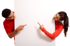 Playful young couple pointing the blank board Stock Photo