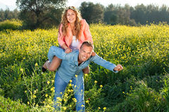 Playful young couple riding piggy back royalty free stock image
