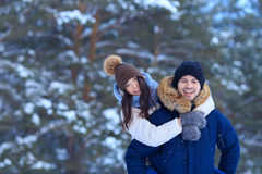 Playful young couple walking in winter forest Stock Photos