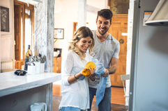 Playful young couple washing dishes. Young cheerful couple playing at kitchen while washing dishes together Royalty Free Stock Photo