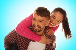 Playful young couple with woman riding piggyback Stock Photography