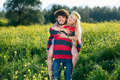 Playful young couple in a yellow rapeseed field. Royalty Free Stock Photography