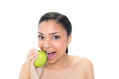 Playful young dark haired model eating a green apple Royalty Free Stock Image