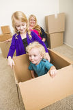 Playful Young Family In Empty Room Playing With Moving Boxes.  Royalty Free Stock Photography