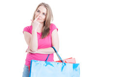Playful young female carrying shopping bags and touching her nos Royalty Free Stock Images