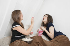 Playful young female throwing popcorn into friend's mouth in bed Stock Photography