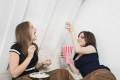 Playful young female tossing popcorn into friend's mouth in bed Stock Images