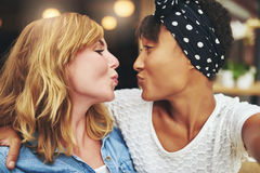 Playful young girl friends puckering up for a kiss Stock Photo