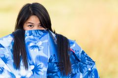 Playful young girl peeking over her. Playful young Thai girl peeking over the top of her blue umbrella or sunshade with an amused look as she plays outdoors in Royalty Free Stock Image