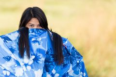 Playful young girl peeking over her. Playful young Thai girl peeking over the top of her blue umbrella or sunshade with an amused look as she plays outdoors in Royalty Free Stock Photo