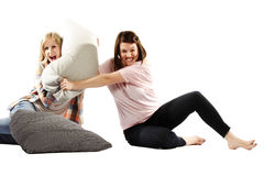 Playful young girls involved in a pillow fight Stock Images
