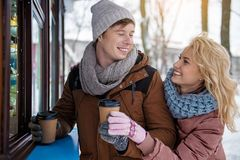 Cheerful guy treating his girlfriend with hot beverage stock images